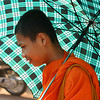 A monk with an umbrella near the Golden Banana Boutique Resort