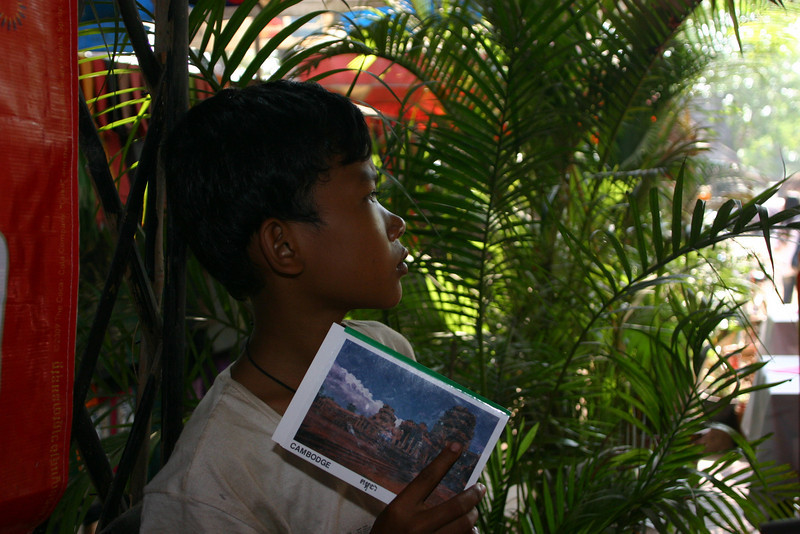 A boy selling postcards at a restaurant near Angkor Wat.   He stood there for nearly the whole time we were eating, hoping we'd buy his postcards.    I gave him some money for letting me take his picture, though I don't think he understood.