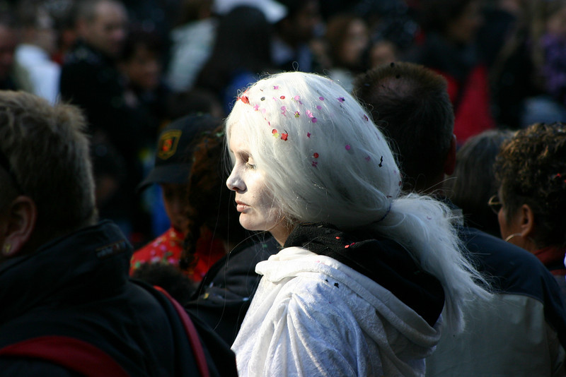 Person in crowd.   The stark white against the dark background, and the closed eyes, made her look like a ghost -- in the crowd, but other-worldy.