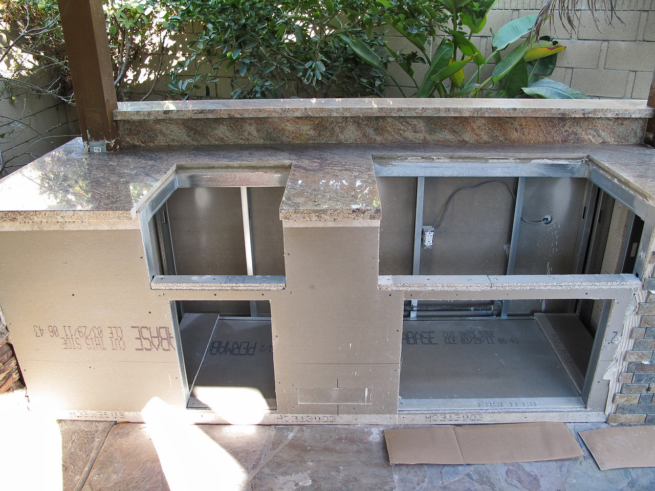 Before the granite came, we installed all the new electrical wiring, new gas pipes and the shut-off valve now is conveniently located outside at the back of the island.<br /> A shelf was added on the back splash. The holes were cut ready for the BBQ grill and the power burner.