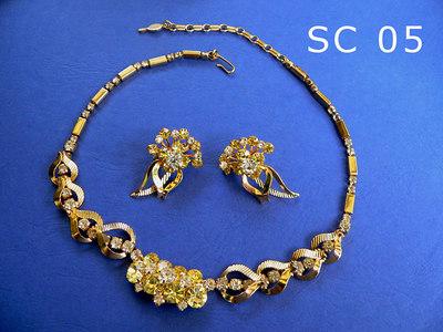 SARAH COVENTRY semi-parure composta da girocollo regolabile siglato SC al ciondolo di chiusura ed orecchini a clip metallo color oro, strass trasparenti e color zaffiro