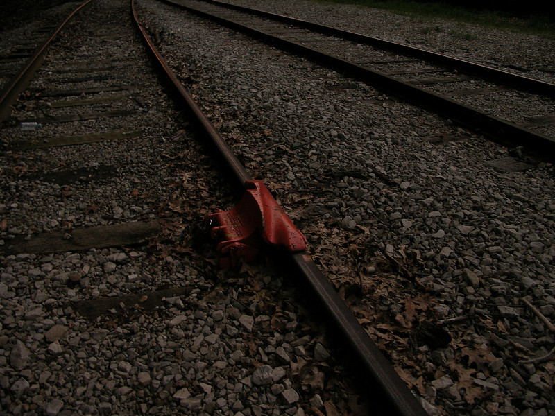 This device seems to be a train-derailler, locked to the track.  Weird!