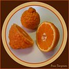 00aFavorite Pixie Tangerines - 1 cut in half, 1 intact [circular border, wood grain texture, text]