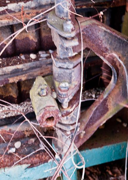 Rusty linkage on underside of old railcar.