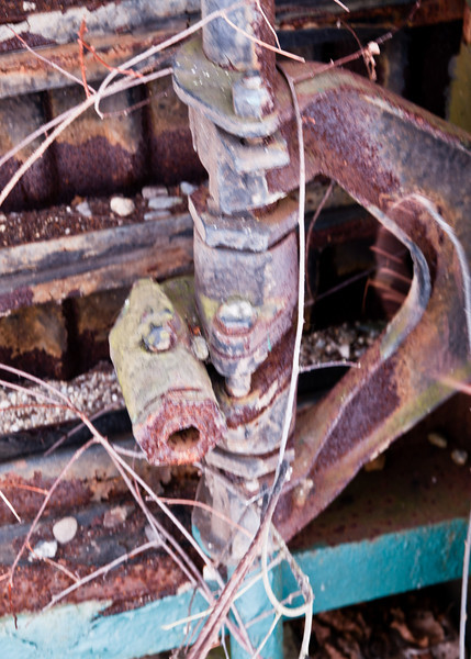 Rusty linkage on underside of old railcar.