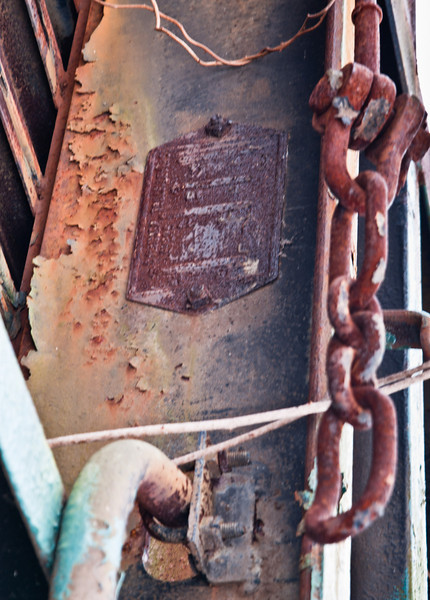 Chain and label on underside of old railcar.