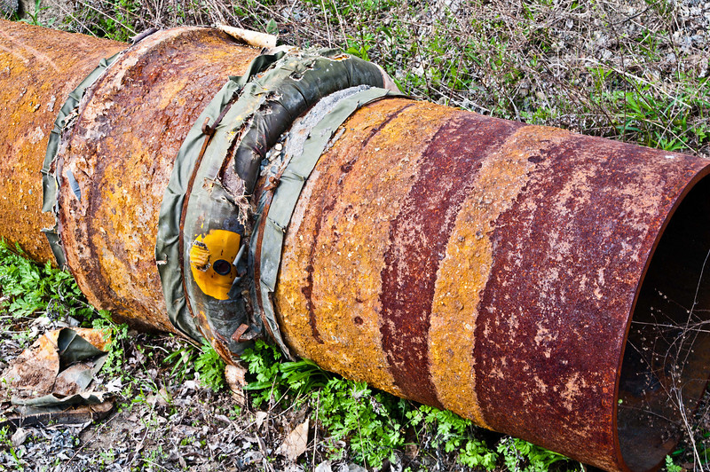 Rusty old Gas Line pipe with signs of ancient repair.