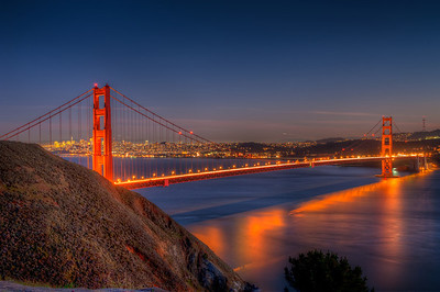 This shot of the Golden Gate Bridge was capture just after the December evening sunset, The light haze over the city captured the glow from the city lights as the water reflects the glow from the bridge lights. aken in december 2012, to the north west of the bridge.