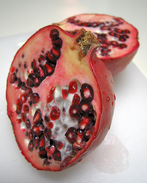 Pomegranate half with other half in bg