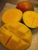 Cut mangoes and an intact mango [right bg blurred]
