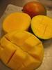 Cut mangoes and an intact mango [right bg blurred]