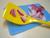 Red onions, yellow spatula, blue cutting board