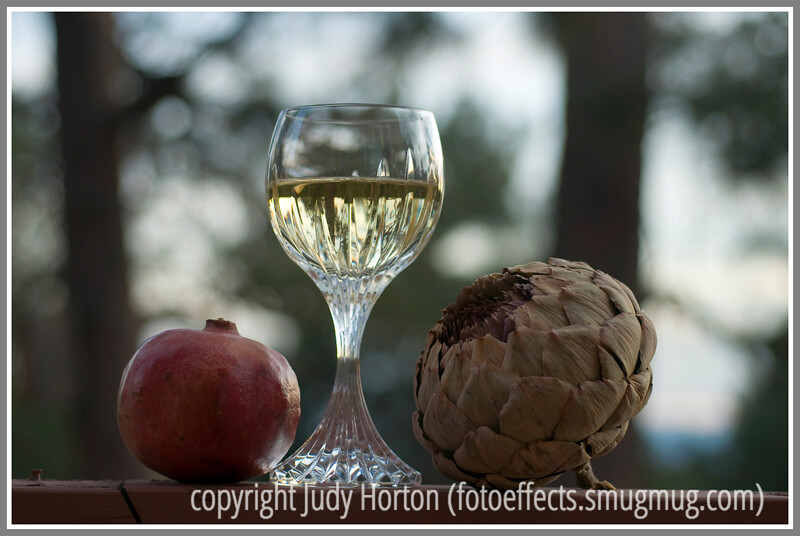 Still life with baccarat crystal, white wine, pomegranate and dried artichoke; background of forest at sunset