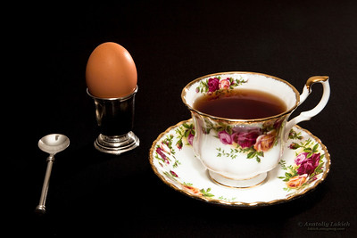 Fancy coffee cup and egg. Breakfast setting of a fancy china coffee cup and saucer with spoon and egg in silver cup isolated against a black background.