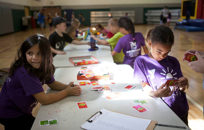 First graders Victoria Alexander and Aaliyah Gunnison play the game Apples to Apples during day camp at the YMCA in Chandler, Arizona.