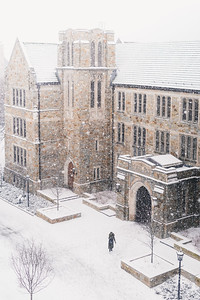 A student walks into Fulton Hall during a light snow storm.