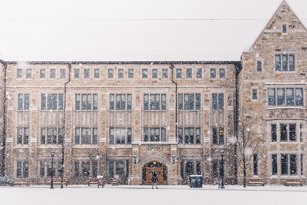 A student walks past Stokes Hall during a light snow storm.