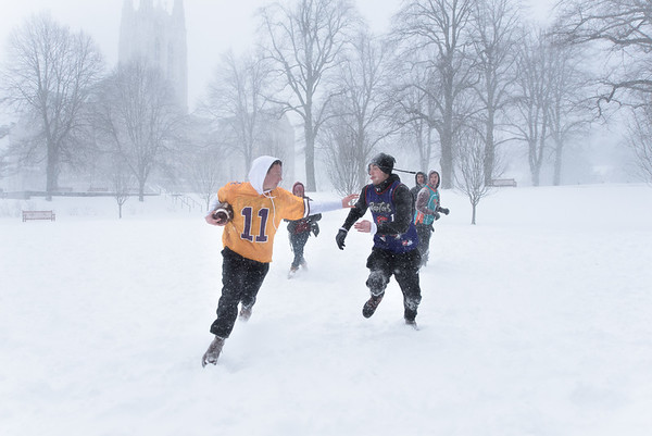 2017 Snow day at Boston College. Students playing football on the lawn.