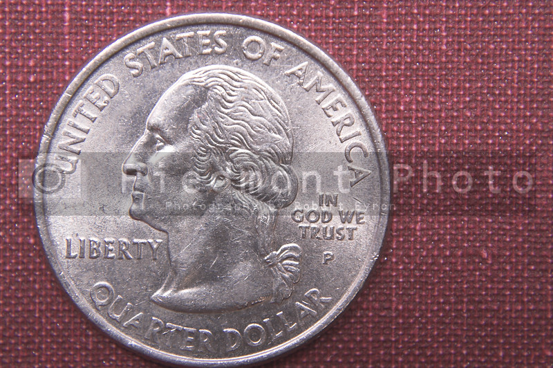 A United States currency quarter of a dollar.