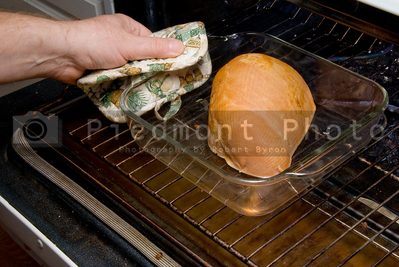 A cook removing a baked ham from the oven.