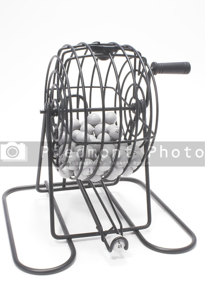 A bingo game cage with numbered balls.