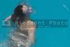 A girl swiimming in a pool of water.