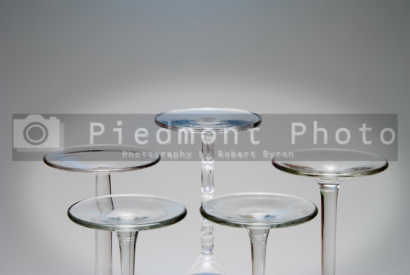 A set of assorted wine glasses turned upside down.