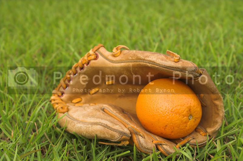 A delicious orange in a baseball glove.