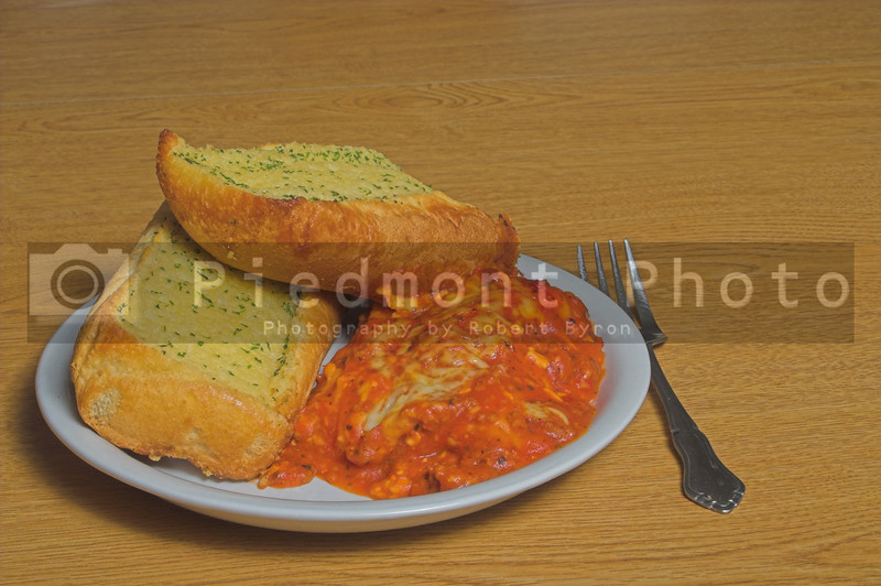 A large portion of Italian lasagna and garlic bread.