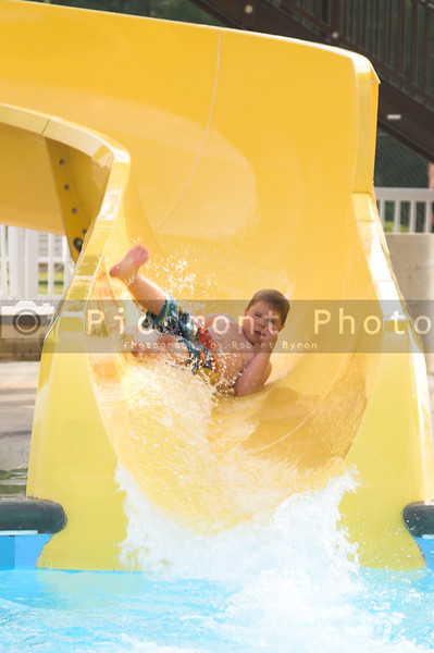 A young boy sliding down a water slide.