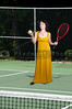 A beautiful woman in a formal evening gown playing the sports game of tennis