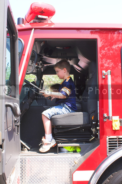 A young boy sitting in a fire truck.