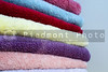 A stack of assorted colored trry cloth towels.
