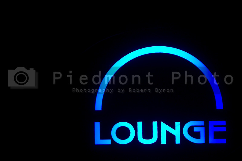 A neon lounge sign outside of a bar.