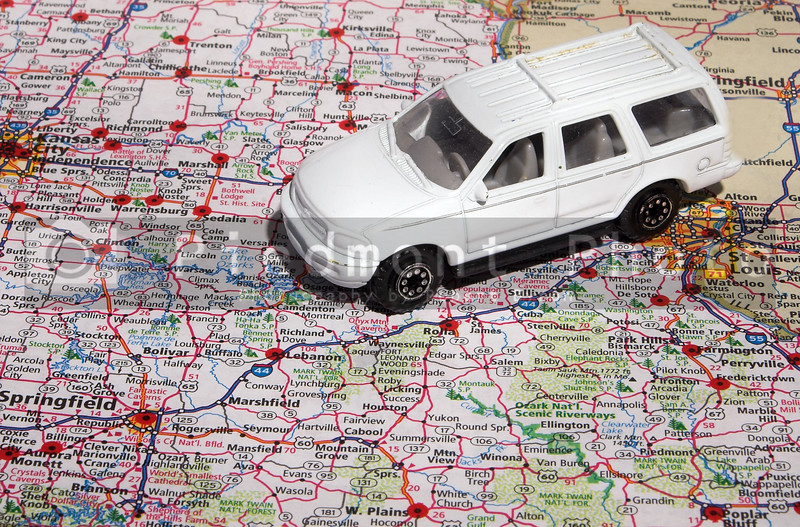A toy car travrling across an American road atlas.