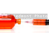 A prescription medicine vial and a syringe.