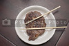 Japanese steak on a plate with chopsticks.