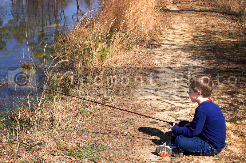 A litlle boy fishing in a pond.