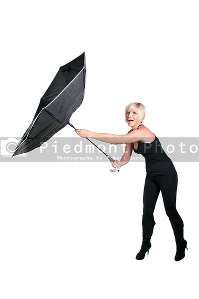 A beautiful woman holding a black torn umbrella