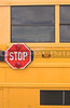 The stop sign on the outside of a school bus.
