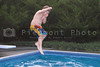 A little boy jumping into a pool.