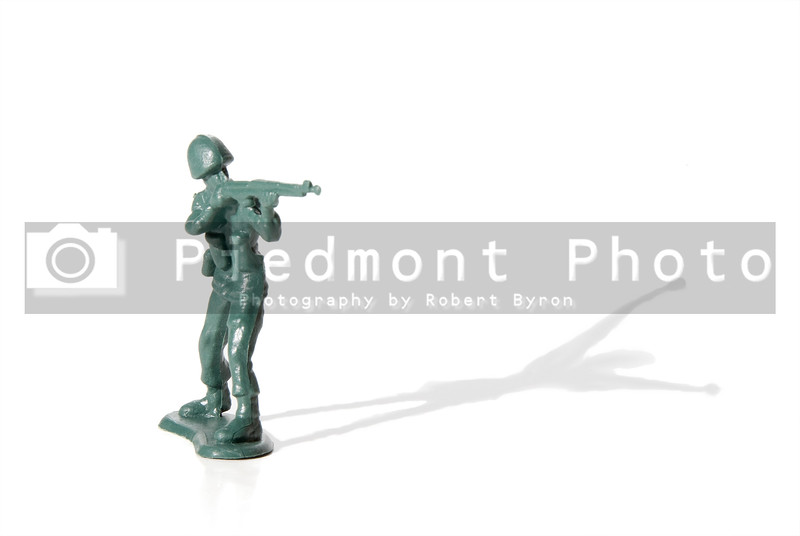 A toy soldier in battle with his shadow surrendering.