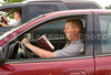 A man reading a book as he drives.