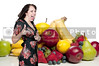 A beautiful young woman in front of a wide assortment of delicious and fresh fruits