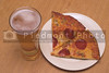 A slice of pizza and a beer in a pilsner glass.