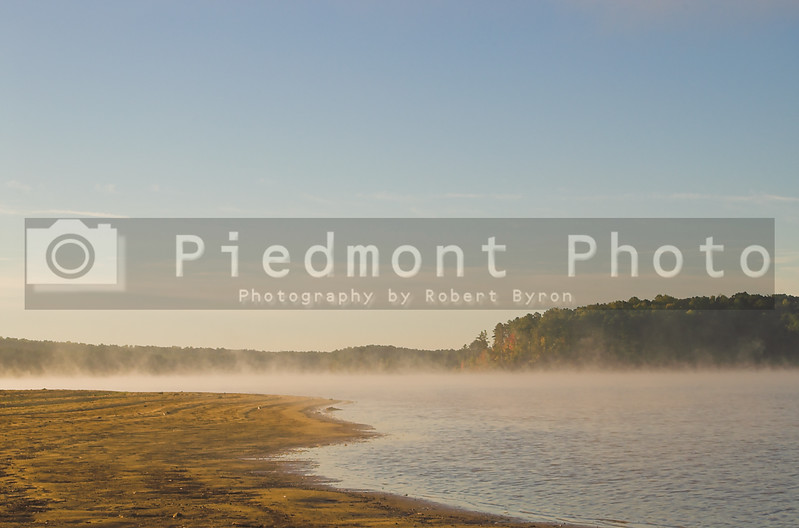 A misty fog over a lake in the early morning.