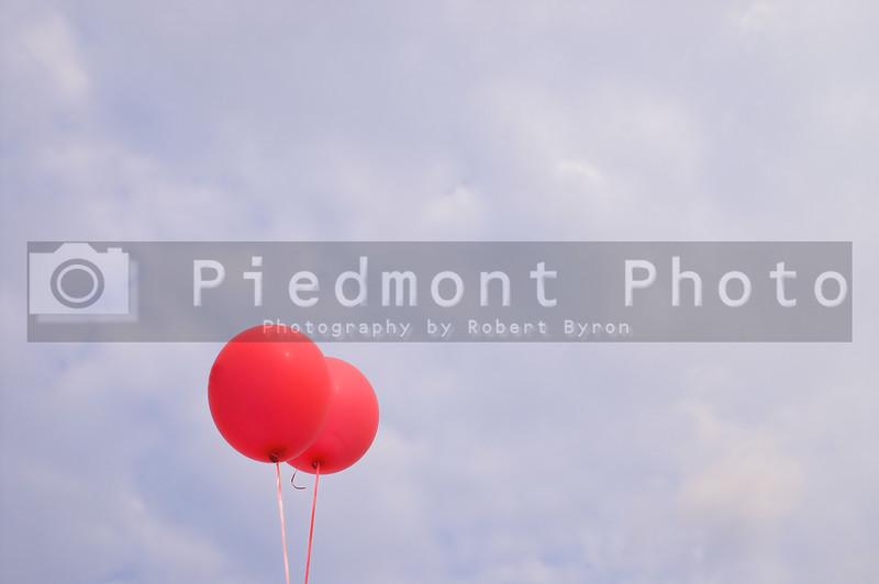 Balloons agianst a cloudy blue summer sky.