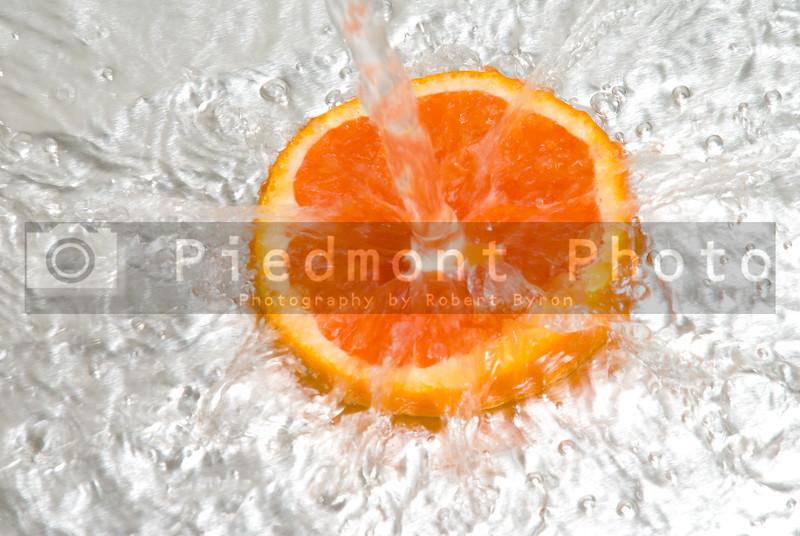 An orange slice under a stream of water.