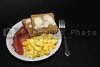 A delicious breakfast of bacon, eggs and toast.