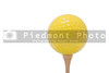 A yellow golf ball on a golf tee.